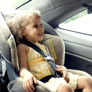 Young cute female child in back seat car set