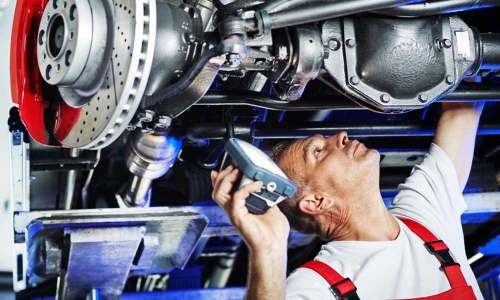 Garagiste qui regarde sous une voiture