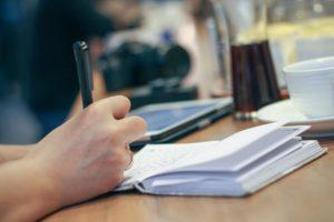 main qui écrit dans un carnet